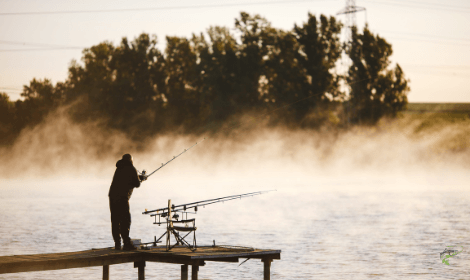 Carp fishing in the wind - man casting into windy lake