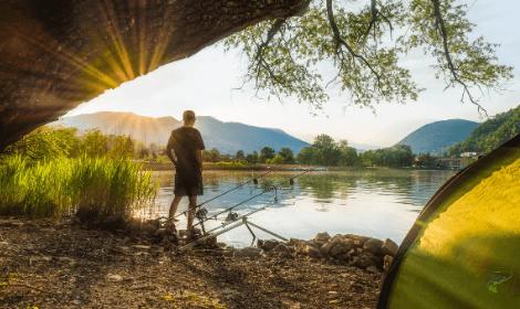 Summer carp fishing tips - Sunny lake with carp fisherman