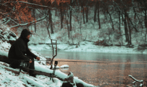 Do Carp Feed in the Winter - Man sitting by lake in the snow