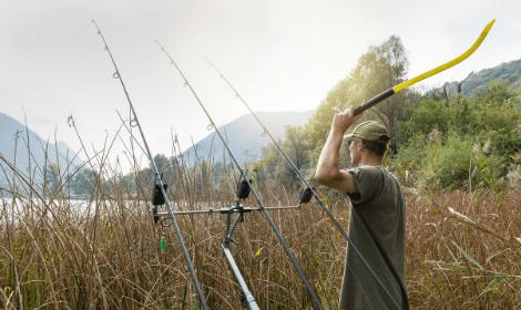 Pre-baiting for carp - fisherman using throwing stick