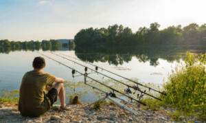 How to Catch Carp from Rivers - man sitting beside river with carp rods