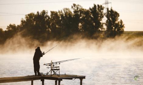 Carp fishing tips - man casting into windy lake