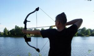 how-to-bow-fish-for-carp-man-shooting-bow-beside-river