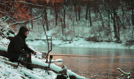 When are carp most active - Man sitting by lake in the snow
